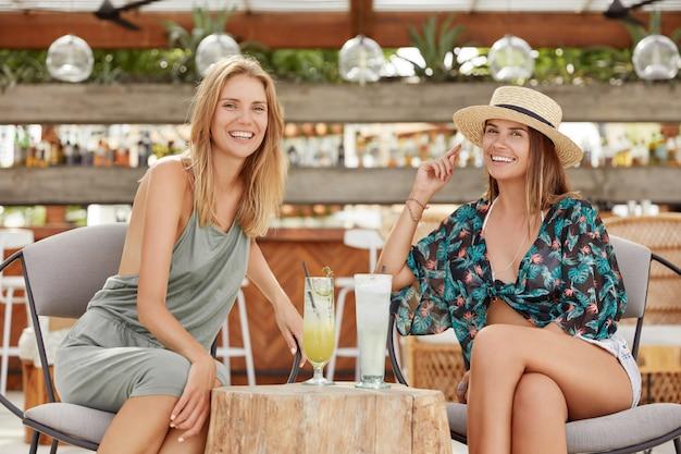 ポジティブな若い女性は屋外のカフェテリアやバーに座って、新鮮な夏のカクテルを飲み、楽しい会話をし、再現し、ポジティブな表現をしています。レズビアンは一体感を楽しみ、デートやパーティーをする 無料写真