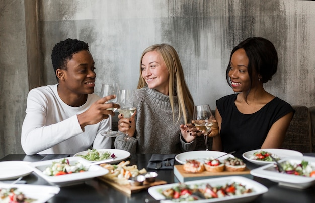 Positive young friends having wine at dinner Free Photo