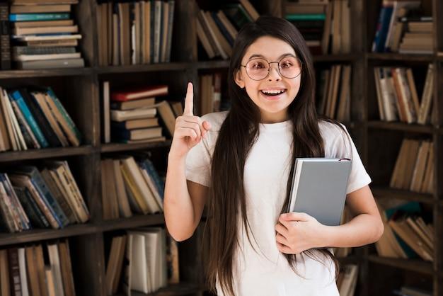 Положительная молодая девушка держит книгу в библиотеке Бесплатные Фотографии