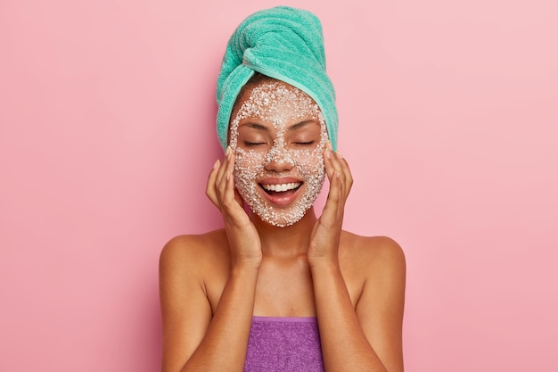 Positive young lady massages face with special scrub, reduces dark dots on cheeks, feels pleasure from beauty treatments, has skin problem, cares about hair, wrapped in towel. high resolution Free Photo
