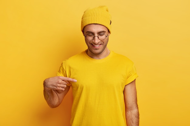 Il giovane maschio positivo indica lo spazio vuoto della maglietta, mostra lo spazio per il tuo design o logo, sorride volentieri, indossa gli occhiali, vestito giallo, concentrato verso il basso Foto Gratuite