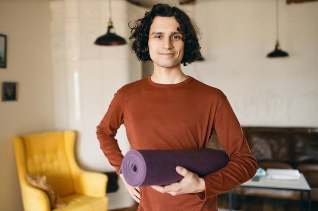 腕の下にヨガマットのロールを持ってカジュアルな服を着たポジティブな若い男は、屋内で練習し、検疫中に家にいて幸せで、自己啓発と健康的な活動により多くの時間を費やしています 無料写真