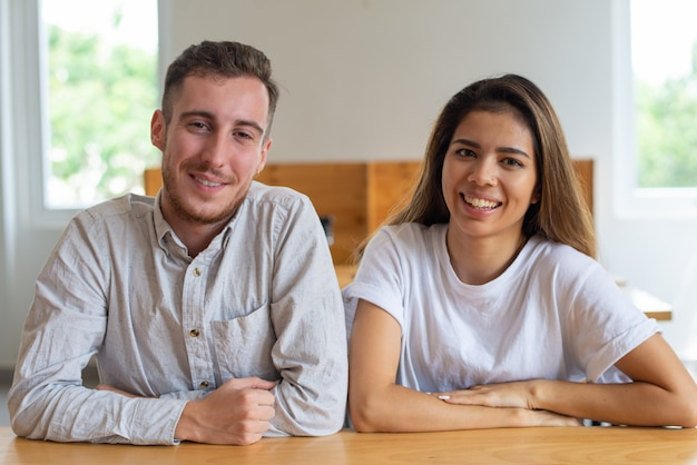 Positive young man and woman sitting at table and posing Free Photo