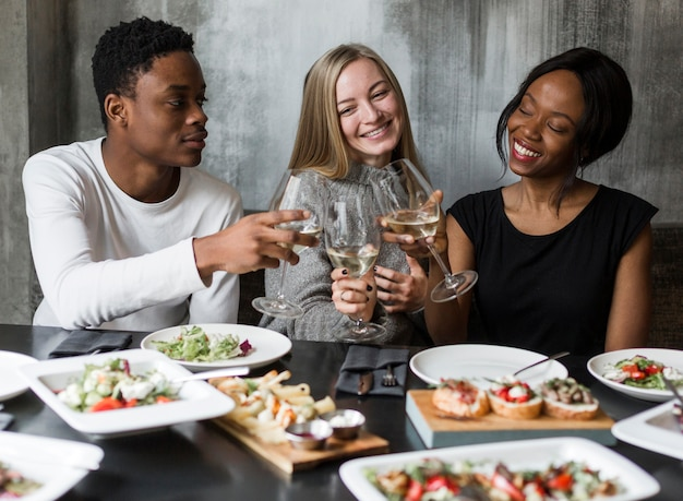 Positive young people having dinner together Free Photo