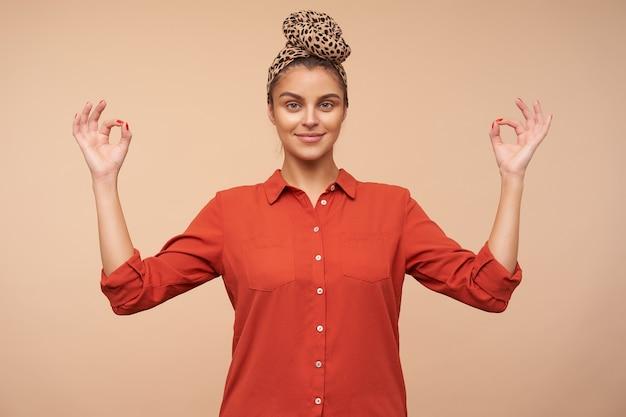 ベージュの壁に隔離されたムードラジェスチャーで前を見て、指を折りたたむ間、ヘッドバンドがわずかに笑っているポジティブな若いかなり茶色の髪の女性 無料写真