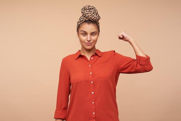Positiva giovane donna graziosa del brunette con trucco naturale socchiudendo gli occhi mentre guarda davanti e tenendo la mano alzata, in posa sul muro beige Foto Gratuite