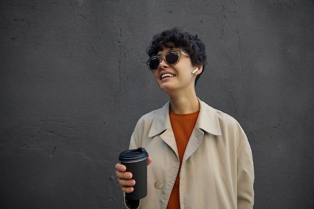 通りを歩きながら、仕事を始める前にホットコーヒーを飲みながら、流行の服とスタイリッシュなサングラスを身に着けている短い巻き毛のポジティブな若いかなり暗い髪の女性 無料写真