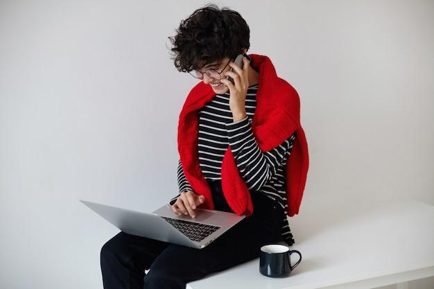 그녀의 다리에 노트북과 함께 앉아 흰색 배경 위에 포즈를 취하는 동안 전화 대화를 나누는 긍정적 인 젊은 꽤 짧은 머리 곱슬 갈색 머리 여자 무료 사진