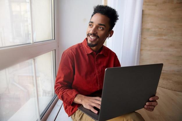 창턱에 앉아 창 밖을 기쁘게 보는 동안 그의 무릎에 노트북을 유지하는 어두운 피부를 가진 긍정적 인 젊은 짧은 머리 수염 갈색 머리 남자 무료 사진