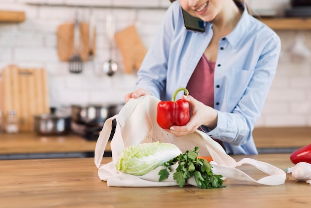 Positive young woman proud of organic groceries Free Photo
