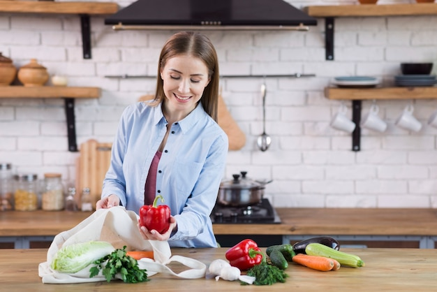 Positive young woman proud of organic vegetables Free Photo