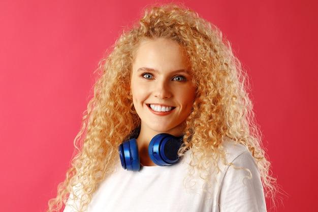 孤立した青いヘッドフォンで立っているポジティブな若い女性 Premium写真