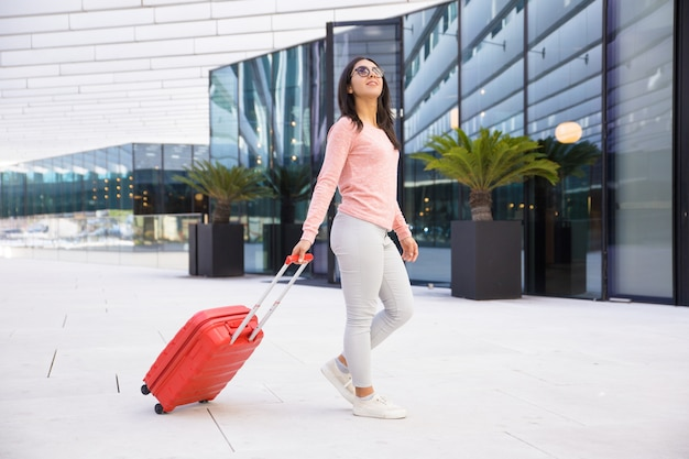 Positive young woman in sunglasses leaving airport hall Free Photo
