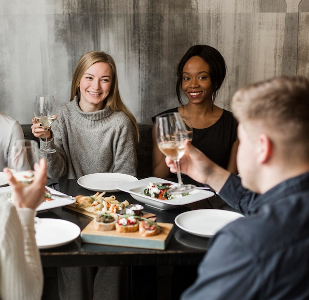 Positive young women smiling at dinner party Free Photo