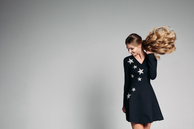 Positivity woman  in fashionable black dress with stars dancing. Premium Photo