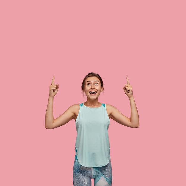 기쁜 표정을 지닌 Positve 유럽 여성, 두 검지 손가락을 위로 향하게하고 캐주얼 조끼와 레깅스를 입은 모델, 분홍색 벽 위에 모델. 광고 개념. 천장 좀 봐! 무료 사진