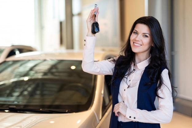 カーディーラーで彼女の新しい車の近くのキーを持つpossing幸せな女性バイヤー Premium写真