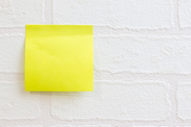 Post it note or sticky note on white wallpaper brick pattern use for background Premium Photo
