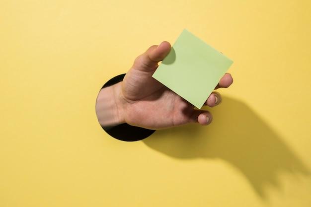 Вид спереди рука, держащая post-it Бесплатные Фотографии