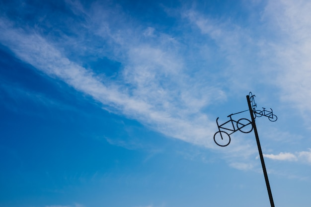 Post with the figure of some bicycles indicating the road, with blue sky and clouds in the background. Premium Photo