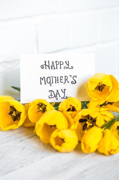 はがき母の日と軽い木製の背景、休日の概念に黄色のチューリップ 無料写真