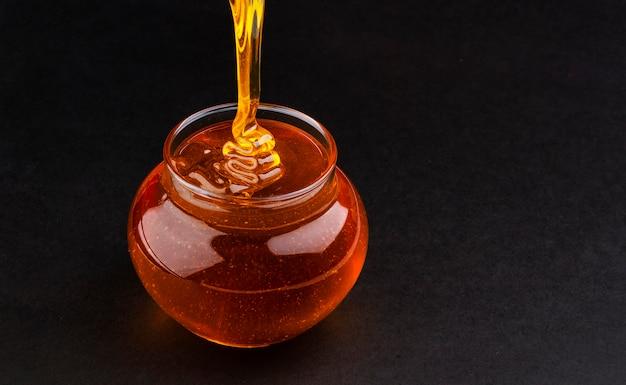 Pot of pouring honey on black Premium Photo