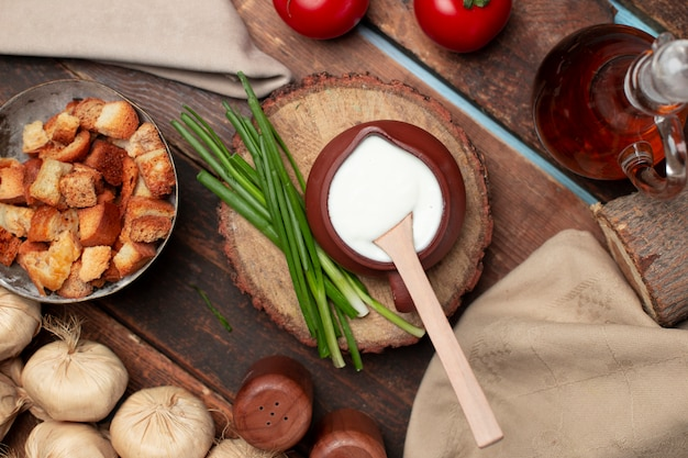 A pot of yogurt with herbs and crackers on the wooden table Free Photo