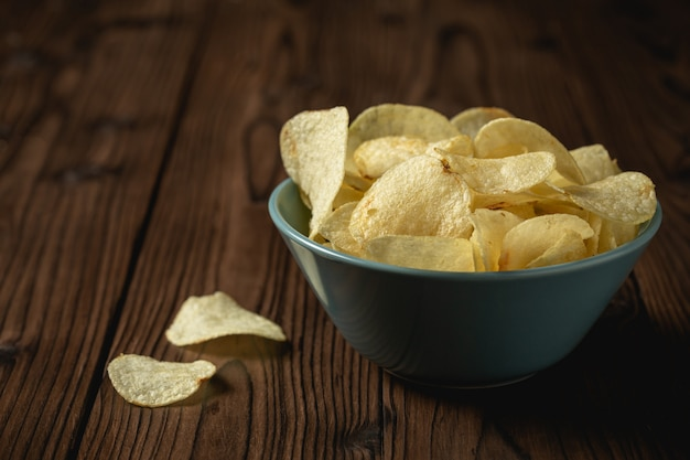 Potato chips in bowl on a wooden table. Free Photo