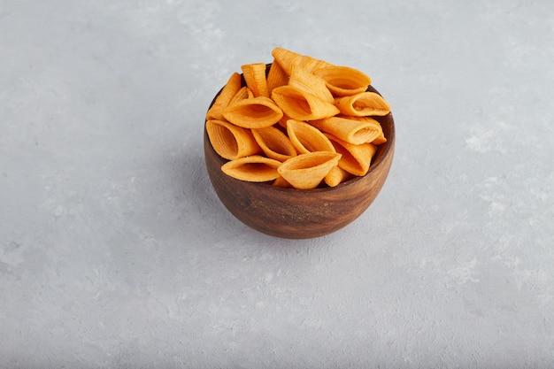 真ん中の木製ボウルにポテトチップス。 無料写真