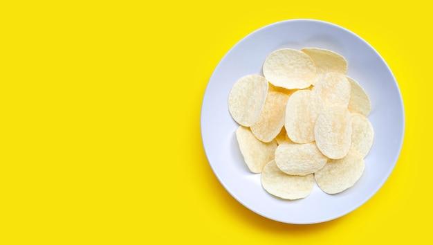 黄色の背景にポテトチップス。上面図 Premium写真