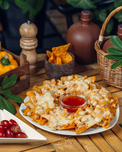 Potato chips with melted cheese and tomato sauce. Free Photo