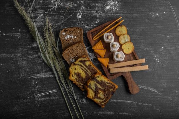木製の大皿とパンのスライスはさておき、上面にペストリー製品とポテトチップス 無料写真