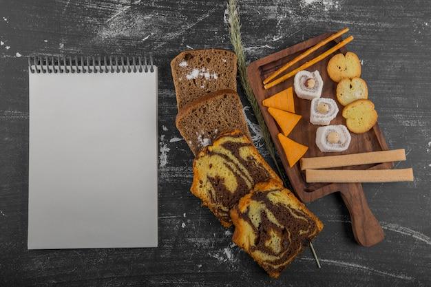 木製の大皿にペストリー製品を添えたポテトチップスと領収書と一緒にパンのスライス 無料写真