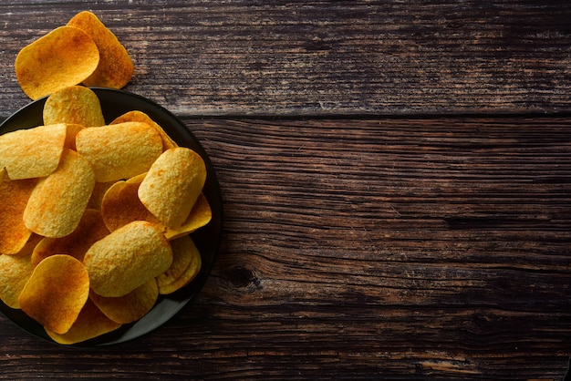 Potato chips over wooden background. salty crispy snack. copy space. Premium Photo