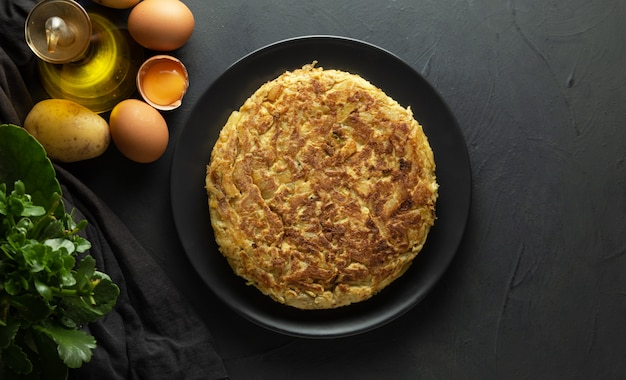 Potato omelet on dark wooden background Premium Photo