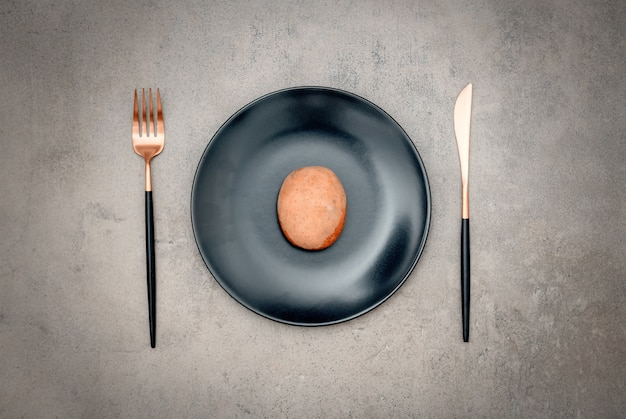 Potato in a plate with knife and fork Premium Photo