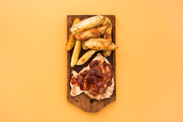 Potato wedges and meat with sauce on wooden board Free Photo