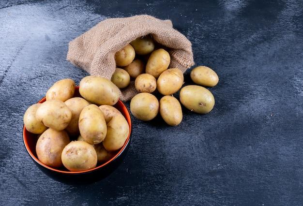 Картофель в мешке и миске на темном столе Бесплатные Фотографии