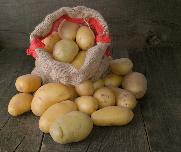 Potatoes on a little bag among other potatoes on rustic wooden background Premium Photo