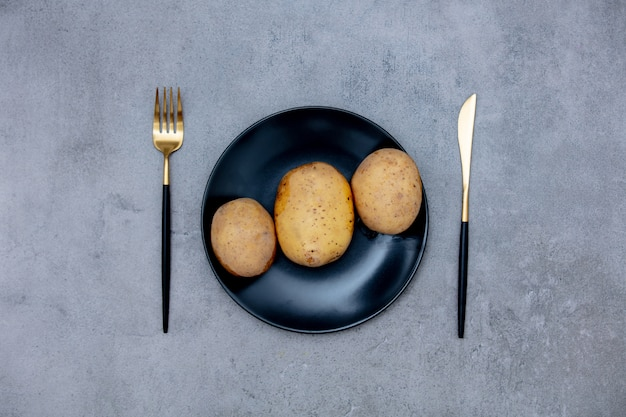 Potatoes in a plate with knife and fork Premium Photo