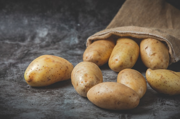 Potatoes pour out of sacks on gray floor Free Photo