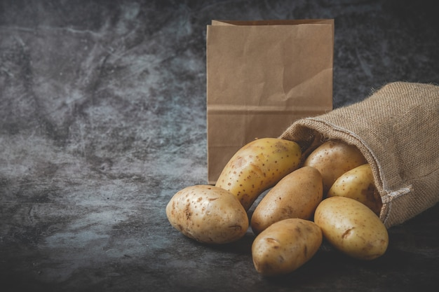 Potatoes pour out of sacks on gray floor Free Photo