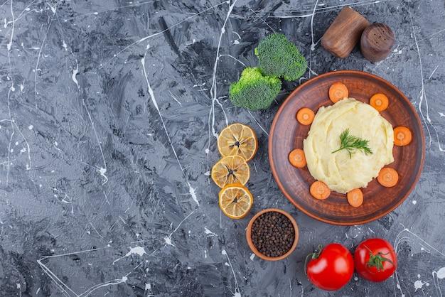 파란색 표면에 야채와 양념 그릇 옆에 접시에 감자 퓌레와 얇게 썬 당근 무료 사진
