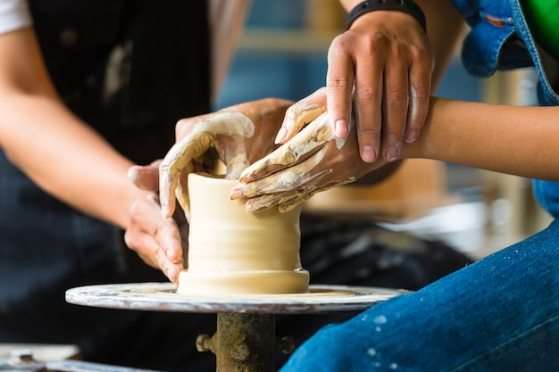 Potter creating clay bowl on turning wheel Premium Photo