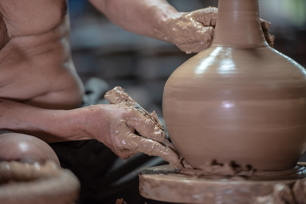 Potter doing pottery on a potter wheel in the factory Premium Photo
