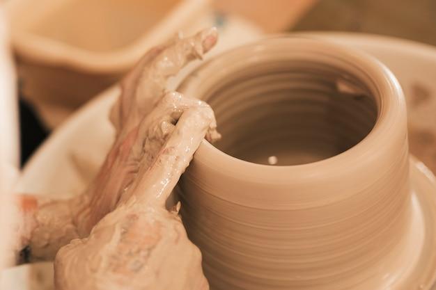 Potter making ceramic pot on the pottery wheel Free Photo