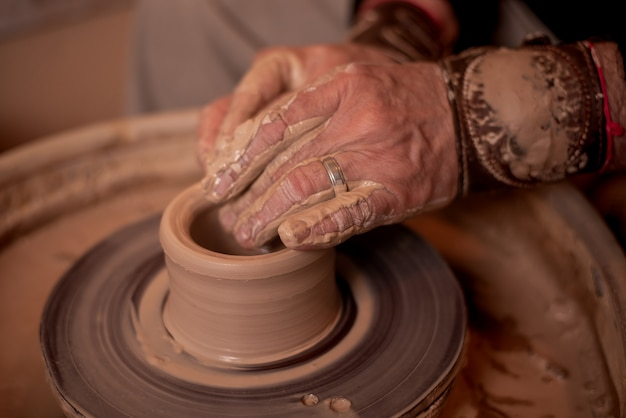 Potter's hands work with clay, making it a product Premium Photo