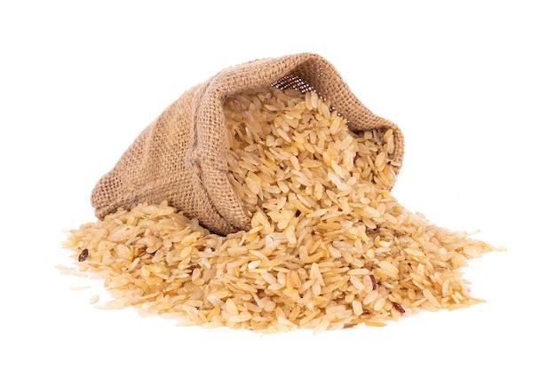 Измельченный незрелый рис в джутовом мешке, изолированные на белой поверхности Premium Фотографии