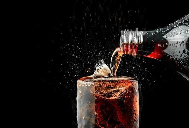 Pour soft drink in glass with ice splash on dark background. Premium Photo