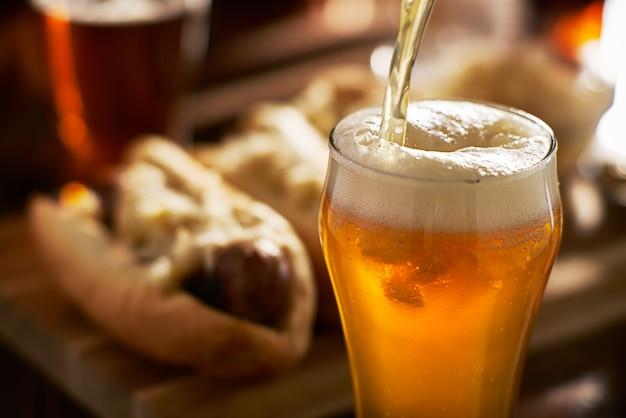 バックグラウンドでソーセージとマグカップに琥珀色のビールを注ぐ Premium写真